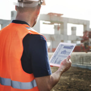 Checking blueprints on a tablet on site - wearing an orange vest and helmet