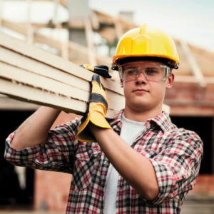 Employee carrying timber on site - wearing safety gloves, hat and glasses- manual handling