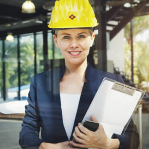 Management on site with hard hat, clipboard and phone